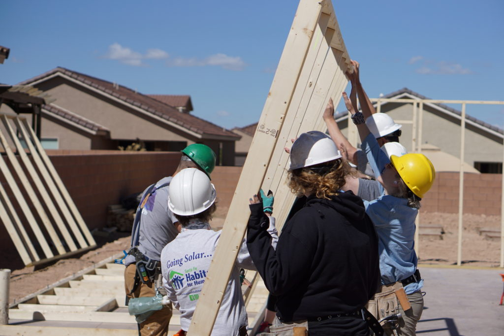 Volunteers raise a wall frame