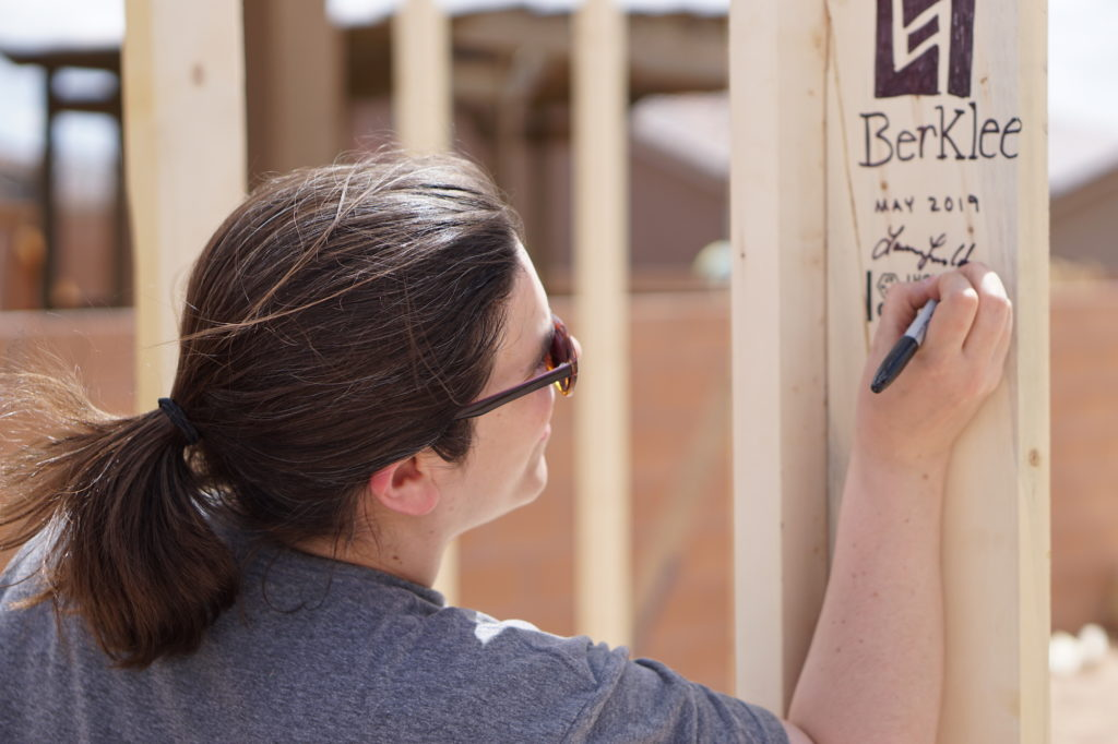 Volunteers write their names on the house frame