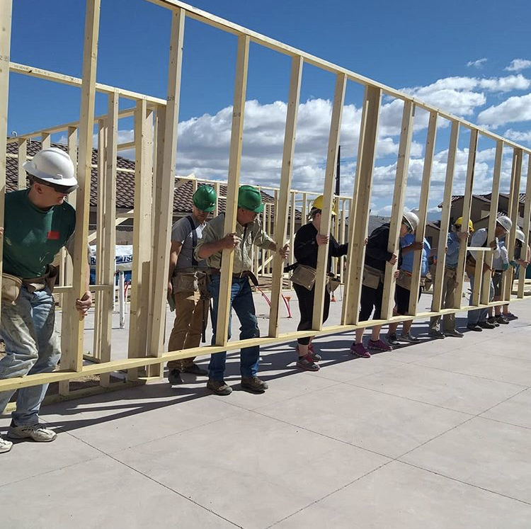 Habitat for Humanities workers lift a house frame